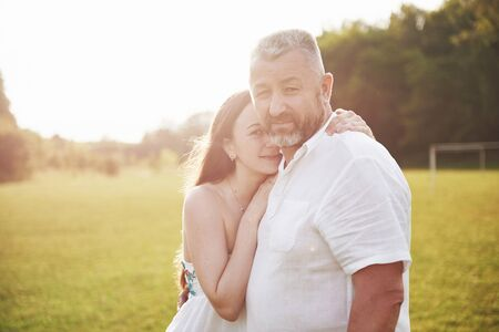 An elderly man hugged his adult daughter outdoors. Foto de archivo