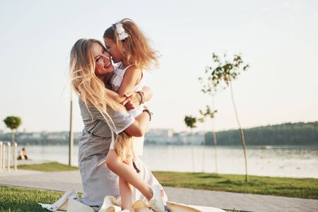 Happy young mother with a playful daughter in a park near the water.