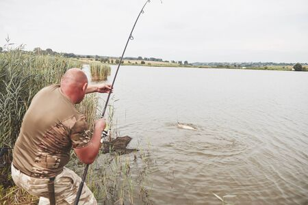 The fisherman caught a big fish of the carp and pulled it to the shore. Hunting and hobby sport.