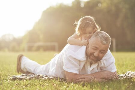 A cute little girl is spending time with her beloved grandfather in the park. They had a picnic on the grass.