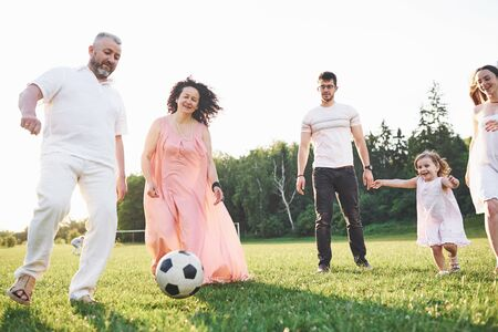 Relax with the whole family. Several gender generations came together for a walk in the park. Granddaughter and grandfather play football.