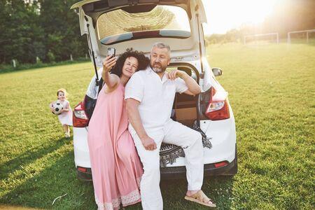El abuelo y la abuela se sientan juntos en la naturaleza cerca del automóvil. Hacen una foto selfie y su nieta juega con ellos.