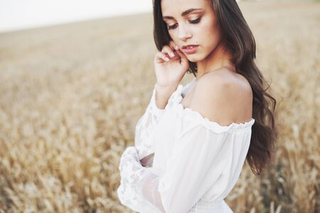 Young sensitive girl in white dress posing in a field of golden wheat. 版權商用圖片