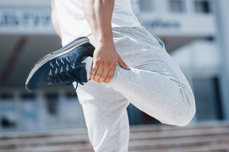 A handsome fitness man in a sportswear, doing stretching while preparing for serious exercise in the modern city.