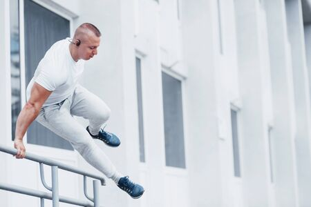 Young sports man doing parkour in the city.