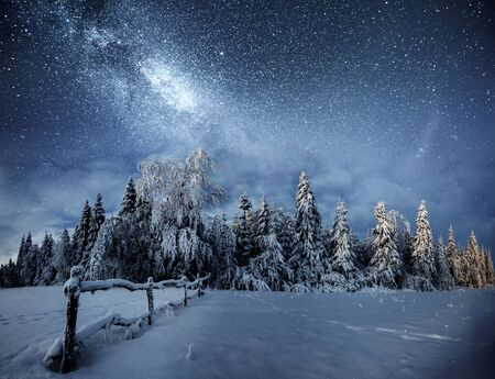 Winterlandschaft. Bergdorf in den ukrainischen Karpaten. Lebhafter Nachthimmel mit Sternen, Nebel und Galaxie. Deep-Sky-Astrofoto. Standard-Bild
