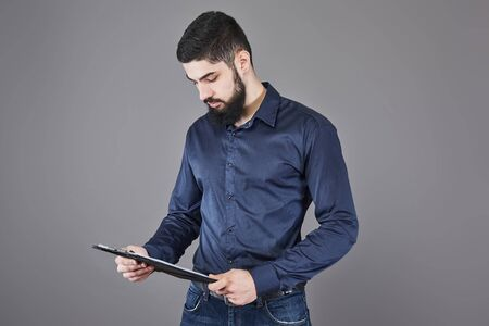 Concentrated young attractive businessman in blue shirt planning and writing in clipboard.