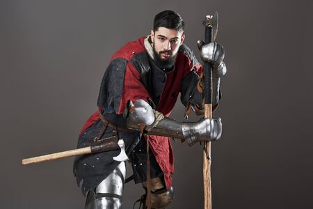 Medieval knight on grey background. Portrait of brutal dirty face warrior with chain mail armour red and black clothes and battle axe. Stockfoto