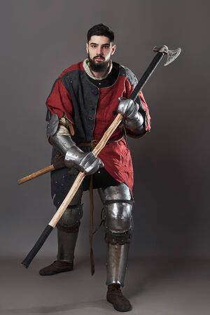 Medieval knight on grey background. Portrait of brutal dirty face warrior with chain mail armour red and black clothes and battle axe. Banco de Imagens - 134828279
