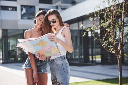 Young girls reading city map and looking for hotel. Lovely tourists with backpacks determine the concept of knowledge of the world. Reklamní fotografie