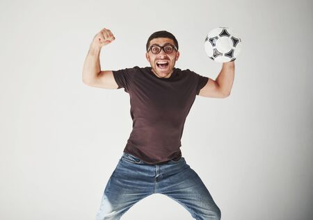 Excited soccer fan with a football isolated on white background. He jumps is happy and performs various tricks of cheering for his favorite team.