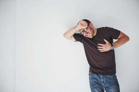 A young guy in casual clothes holds on to the heart and the head, it hurts or he is sick.