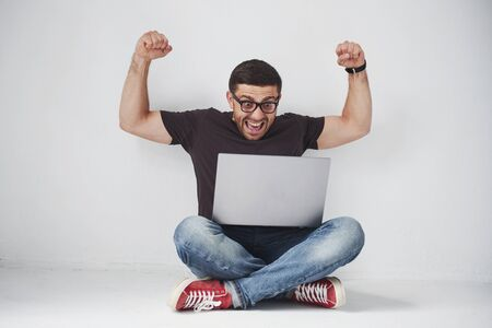 Young caucasian man sitting over white brick wall using computer laptop happy in shock with a surprise face, afraid and excited with fear expression.