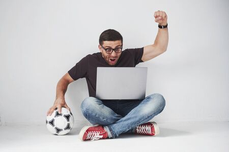 Excited soccer fan with a football isolated on white background. He sits on the floor and watches the results of the game and the best moments of the match on the laptop Banque d'images