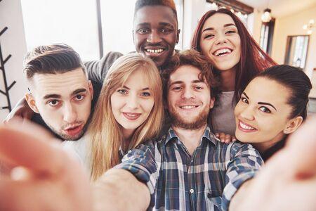 Vrienden die plezier hebben in restaurant. Drie jongens en drie meisjes die selfie maken en lachen. Op de voorgrond jongen met slimme telefoon. Ze dragen allemaal vrijetijdskleding.