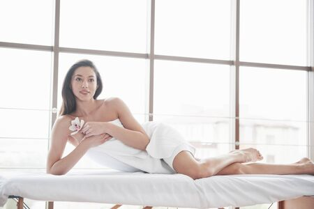 Beautiful young woman relaxing on a towel with a flower of an orchid isolated on a white background. 版權商用圖片
