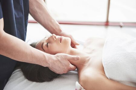 Masseur makes relaxation massage for a neck for a woman