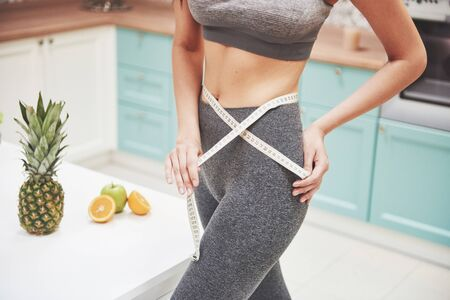 Portrait of a woman measuring her slim body on a kitchen background. Fitness and healthy lifestyle concept. Standard-Bild - 134493179