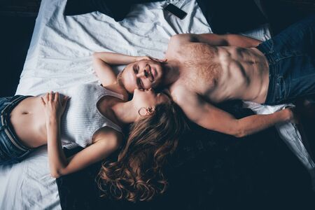 A portrait of a happy young couple who relax in a cozy bed. Banco de Imagens