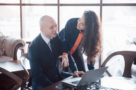 We already have great results. Young beautiful woman pointing at laptop with smile and discussing something with her coworker while standing at office. 版權商用圖片