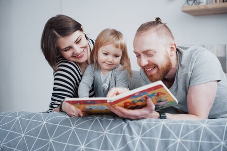 Father, Mother and Little Daughter Reading Childrens Book on a Sofa in the Living Room. Happy big family read an interesting book on a festive day. Parents love their children. Banco de Imagens