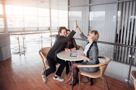 Happy successful business team giving a high fives gesture as they laugh and cheer their success.