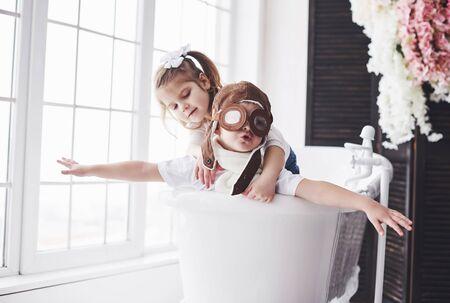 Porträt eines Mädchens und eines Jungen im Pilotenhut, der im Badezimmer bei Piloten oder Matrosen spielt. Das Konzept des Reisens, der Kindheit und der Verwirklichung von Träumen.