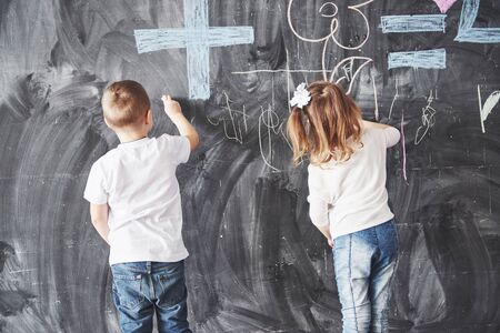 Cute little girl and boy drawing with crayon color on the wall. Works of child. Cute pupil writing on chalkboard. 版權商用圖片