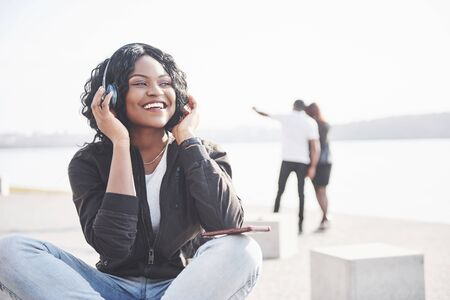 Portrait of a beautiful young pretty African American girl sitting on the beach or lake and listening to music in her headphones. Standard-Bild - 134644905
