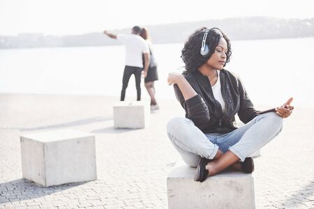 Portrait of a beautiful young pretty African American girl sitting on the beach or lake and listening to music in her headphones. Standard-Bild - 134645278