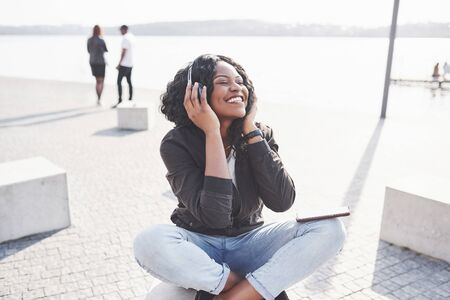Portrait of a beautiful young pretty African American girl sitting on the beach or lake and listening to music in her headphones. Standard-Bild - 134645942