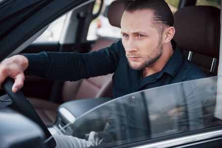 Confident young businessman sitting at the wheel of his new car. Stock Photo