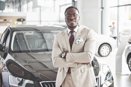 The young attractive black businessman buys a new car, dreams come true. Stock fotó