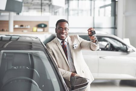 Handsome black man in dealership is hugging his new car and smiling.