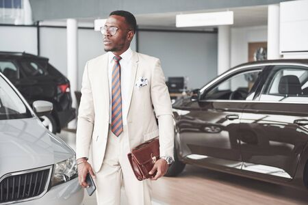 Young black businessman on auto salon background. Car sale and rent concept.