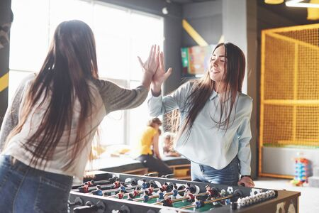 Two beautiful twin girls play table football and have fun. One of the sisters holds a toy ball in his hand and shows the tongue. 写真素材