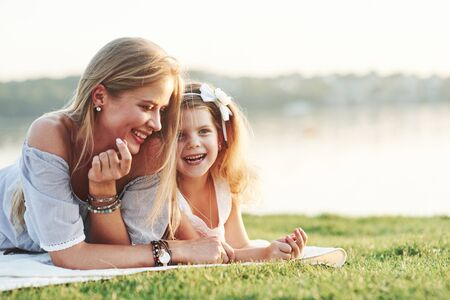 Just heard a joke. Smiling. Photo of young mother and her daughter having good time on the green grass with lake at background.