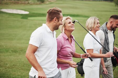 Group of stylish friends on the golf course learn to play a new game. The team is going to rest after the match. Stockfoto