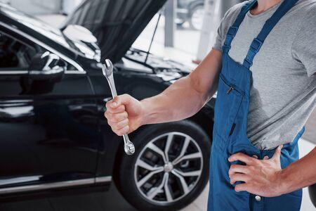 De hand van een automonteur met een moersleutel in een combizone bij de auto in de werkplaats