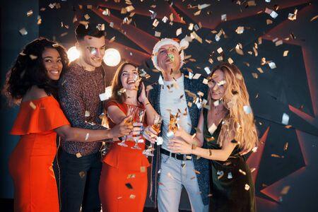 Un gruppo di amici in posa e si diverte con pupazzi di neve e champagne. Festa di Capodanno
