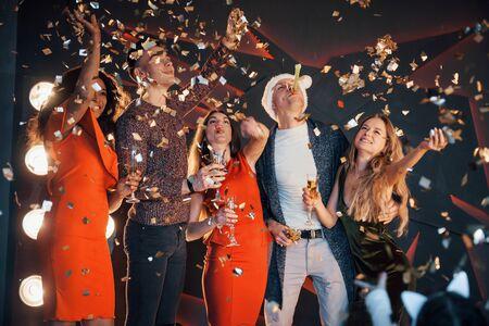 Grupa przyjaciół pozuje i bawi się z bałwanami i szampanem. Obchody Nowego Roku