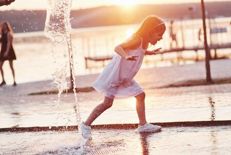 Running through the water. Young girl play in the fountain at the summer heat and lake and woods background.
