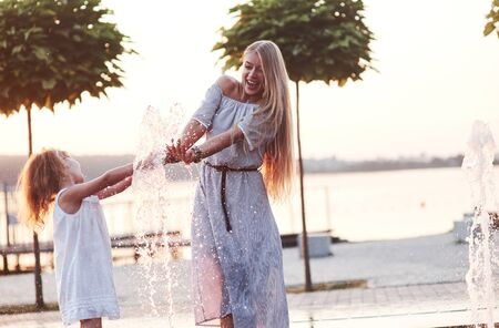 Hot atmosphere. In a hot sunny day mother and her daughter decide to use fountain for cooling themselves and have fun with it. Standard-Bild