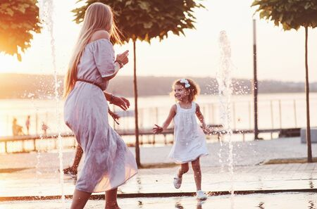 Running and smiling. In a hot sunny day mother and her daughter decide to use fountain for cooling themselves and have fun with it. Zdjęcie Seryjne