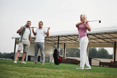 Group of stylish friends on the golf course learn to play a new game.