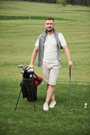A professional player stands on a golf course, holds a metal bag and a golf bag.