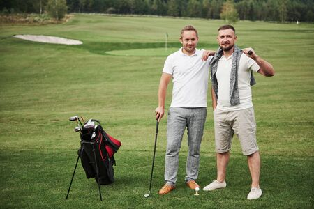 Two stylish men holding bags with clubs and walking on golf course. Reklamní fotografie