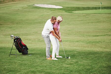 Girl playing golf and hitting by putter on green. Her teacher helps to explore the technique and make her first strikes. Reklamní fotografie