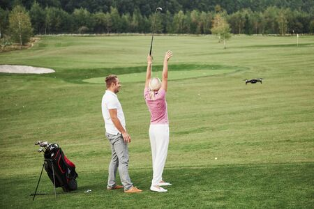Group of stylish friends on the golf course learn to play a new game. Shooting is conducted from the quadrocopter drone Reklamní fotografie