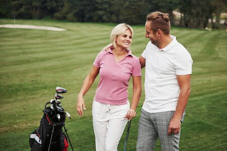 Sportive couple playing golf on a golf course, they stand to the next hole. Reklamní fotografie
